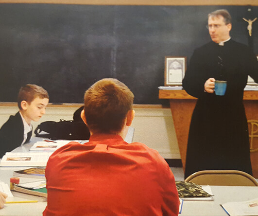 Catholic priest teaching young parishoners about the sacraments of the Catholic Church